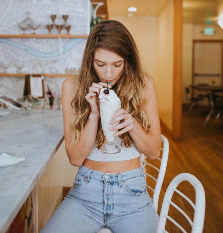 Woman sipping on a milkshake